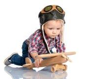 一个试验` s盖帽和一架木飞机的一个小男孩在他的手上 库存图片