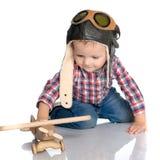 一个试验` s盖帽和一架木飞机的一个小男孩在他的手上 免版税库存照片