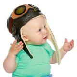 一个试验` s盖帽和一架木飞机的一个小男孩在他的手上 图库摄影