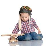 一个试验` s盖帽和一架木飞机的一个小男孩在他的手上 库存照片
