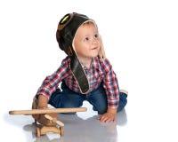 一个试验` s盖帽和一架木飞机的一个小男孩在他的手上 免版税图库摄影