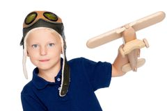 一个试验` s盖帽和一架木飞机的一个小男孩在他的手上 免版税库存图片