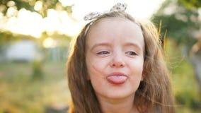 一个诱惑矮小的四岁的女孩显示她的舌头 反对夏天日落背景的特写镜头画象 健康 股票视频