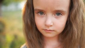一个谦虚,哀伤的小女孩严重看照相机和害羞地投下她的大灰色眼睛 自然秀丽,特写镜头 影视素材