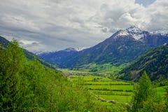 一个谷的一个小村庄与绿色领域和多云天空 免版税库存图片