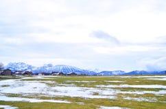 一个谷的小村庄与山和雪在一冷的天 免版税库存图片