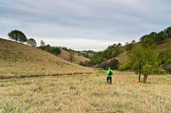 一个谷的远足者在黑暗的云彩下的小小山之间 免版税库存图片