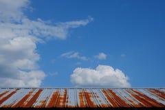一个谷仓的生锈的罐子屋顶反对美丽的蓝天的与puf 免版税图库摄影