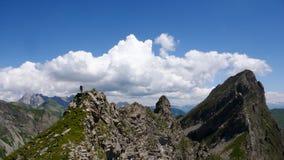 一个象草的土坎的男性登山人在他的途中下来从有一个巨大山风景的一条上升的路线在他后 免版税库存照片