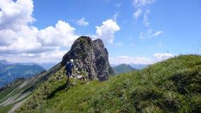 一个象草的土坎的男性登山人在他的途中下来从有一个巨大山风景的一条上升的路线在他后 库存照片