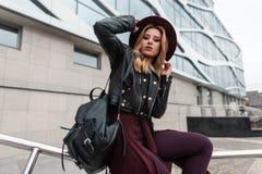 一个豪华帽子的欧洲年轻女人在紫色海角裤子的葡萄酒黑色皮夹克有一个时兴的背包的坐 免版税图库摄影