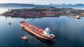 一个货船接近的口岸终端的空中射击在拖曳船帮助下  免版税库存照片