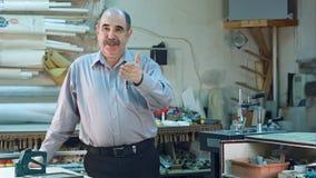 一个资深男性企业主的画象在柜台的他框架车间,身分和谈话后与照相机 免版税库存照片