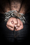 一个赤裸上身的人的手束缚与链子和挂锁 图库摄影