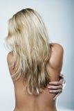 一个赤裸上身的性感的白肤金发的少妇的背面图 库存图片