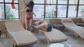一个超重男人和美女从在室内游泳池的一张轻便折叠躺椅起来 股票视频