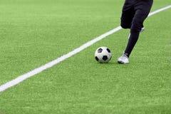 一个足球的特写镜头在行动的在一个绿色橄榄球场 免版税图库摄影
