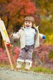 一个跃迁的快乐的小女孩与刷子和油漆,在秋叶公园,绘小孩画 免版税库存照片