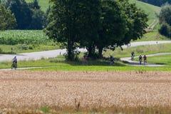 一个距离视图的骑自行车者在一个夏天晴天 免版税图库摄影