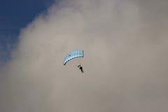 一个跳伞运动员的下降在一朵大云彩的边界的附近 库存图片
