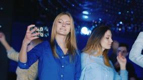 一个跳舞在迪斯科的小组青年人,男人和可爱的妇女棍打 影视素材