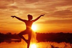 一个跳芭蕾舞者的剪影在日落的 免版税图库摄影