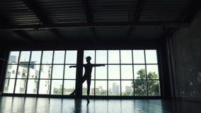 一个跳芭蕾舞者的剪影在窗口背景的 典雅人和美妙地跳舞在的古典芭蕾 股票视频