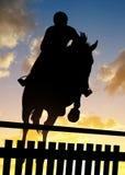 一个车手的剪影在跳过障碍的马的 图库摄影