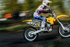 一个车手的特写镜头在摩托车的在赛马跑道乘坐 背景迷离弄脏了抓住飞碟跳的行动 免版税库存照片