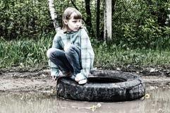 一个轮子的女孩在水坑 库存图片