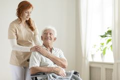 一个轮椅和友好的照料者的微笑的年长人a的 库存照片