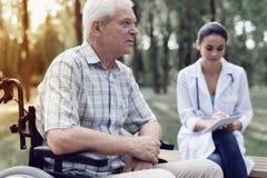 一个轮椅的一个年长人在一位女性医生旁边在夏天公园 库存图片