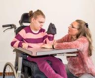 一个轮椅的一个残疾儿童与一名义务关心工作者一起 库存照片