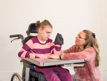 一个轮椅的一个残疾儿童与一名义务关心工作者一起 免版税库存照片