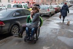 一个轮椅的一个残疾年轻人有女孩的 免版税库存图片