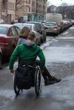 一个轮椅的一个残疾年轻人有女孩的 库存图片