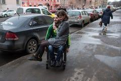 一个轮椅的一个残疾年轻人有女孩的 图库摄影