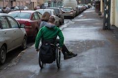 一个轮椅的一个残疾年轻人有女孩的 免版税库存照片