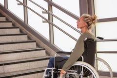 一个轮椅的妇女在台阶前面 免版税库存图片