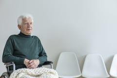 一个轮椅的被麻痹的人在一间候诊室在医院 免版税库存图片