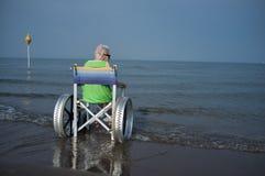 一个轮椅的年长妇女在海 免版税库存照片