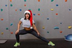 一个运动女孩是在圣诞老人` s帽子,掉下来并且愉快地微笑 免版税库存照片
