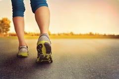 一个运动对在路面的腿在日出或日落期间- 免版税库存照片