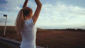 一个运动的女孩一件白色T恤杉的和有长的头发的做在一条几乎空的轨道的呼吸的锻炼在城市之外 股票录像