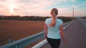 一个运动的女孩一件白色T恤杉的和有长的头发的沿在城市之外的一条空的轨道跑 在休息期间, 股票录像
