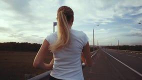 一个运动的女孩一件白色T恤杉的和有长的头发的沿在城市之外的一条空的轨道跑 在的竞技课 股票录像