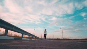 一个运动的女孩一件白色T恤杉的和有长的头发的沿在城市之外的一条空的轨道跑 女孩跑入 股票录像