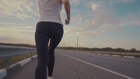 一个运动的女孩一件白色T恤杉的,明亮的运动鞋的和有沿一条空的轨道的长的头发奔跑的在城市之外 股票录像