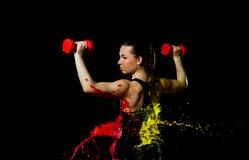一个运动的女孩做着在手的耕种的一锻炼有哑铃的 它在红色和黄色油漆沐浴 免版税库存照片