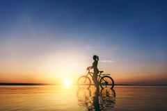 一个运动的女孩的剪影在水中坐一辆自行车在日落在一个温暖的夏日的衣服的 球概念健身pilates放松 天空bac 免版税库存照片